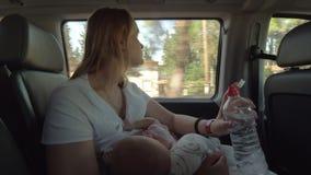 Bemuttern Sie Trinkwasser und Pflegebaby im Auto stock footage