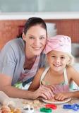 Bemuttern Sie und childing in der Küche, die an der Kamera lächelt Stockfotografie