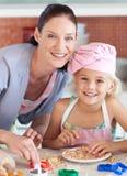 Bemuttern Sie und childing in der Küche, die an der Kamera lächelt Lizenzfreies Stockbild