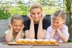 Bemuttern Sie und das unterschiedliche lustige Gefühl von zwei Töchtern, das Ostern-kleine Kuchen betrachtet Lizenzfreie Stockfotos
