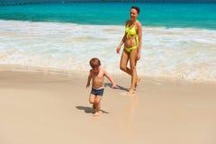 Bemuttern Sie und der Junge mit zwei Jährigen, der auf Strand spielt Stockfoto