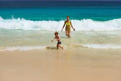 Bemuttern Sie und der Junge mit zwei Jährigen, der auf Strand spielt Lizenzfreie Stockbilder