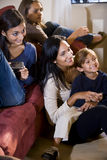 Bemuttern Sie und drei Kinder, die zusammen auf Sofa sitzen stockfoto