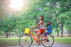 Bemuttern Sie und ein einen.Kreislauf.durchmachenfahrrad der Tochter am Park Lizenzfreie Stockbilder