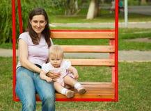 Bemuttern Sie und ein Kind, das in einem Spielplatz schwingt Lizenzfreies Stockfoto
