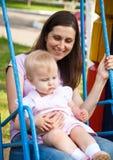 Bemuttern Sie und ein Kind, das in einem Spielplatz schwingt Lizenzfreie Stockfotos