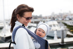 Bemuttern Sie und ein lächelndes nettes Baby in einer Babytrage stockfotografie