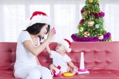 Bemuttern Sie und ihr Baby mit einem Weihnachtsbaum lizenzfreie stockfotos
