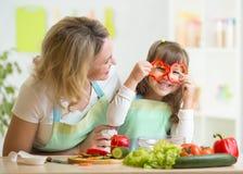 Bemuttern Sie und ihr Kind, das gesundes Lebensmittel zubereitet und Lizenzfreies Stockbild