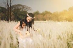 Bemuttern Sie und ihr Kind, das zusammen Gitarre in der Wiesennatur am sonnigen Tag spielt lizenzfreie stockbilder