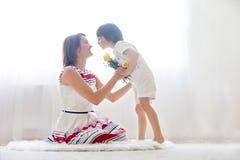 Bemuttern Sie und ihr Kind und mit Weichheit und Sorgfalt umfassen Lizenzfreies Stockfoto