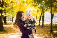 Bemuttern Sie und ihr Kindermädchen, das zusammen draußen auf Herbstweg in der Natur spielt stockfotografie
