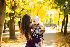 Bemuttern Sie und ihr Kindermädchen, das zusammen draußen auf Herbstweg in der Natur spielt lizenzfreies stockbild