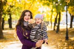Bemuttern Sie und ihr Kindermädchen, das zusammen draußen auf Herbstweg in der Natur spielt stockbild