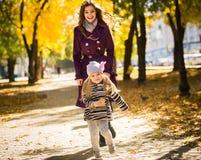 Bemuttern Sie und ihr Kindermädchen, das zusammen draußen auf Herbstweg in der Natur spielt lizenzfreies stockfoto