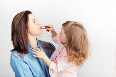 Bemuttern Sie und ihr Kindertochtermädchen mit einem Lippenstift Porträt von stockbilder