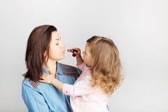 Bemuttern Sie und ihr Kindertochtermädchen mit einem Lippenstift Porträt von stockfotos
