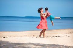 Bemuttern Sie und ihr kleiner Sohn, der auf dem Strand spielt Stockfotografie