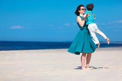 Bemuttern Sie und ihr kleiner Sohn, der auf dem Strand spielt Lizenzfreies Stockfoto