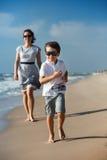 Bemuttern Sie und ihr kleiner Sohn, der auf dem Strand spielt Lizenzfreie Stockfotografie