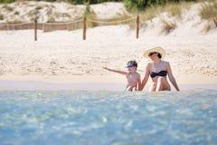 Bemuttern Sie und ihr kleiner Sohn, der in den Meereswogen spritzt Stockfotos