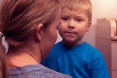 Bemuttern Sie und ihr kleiner Sohn, der nach Streit umarmt lizenzfreie stockfotos
