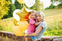 Bemuttern Sie und ihr kleiner Sohn mit Goldballonen am Sommertag Glückliches Familienmutter- und -kinderumarmen Stockfotos