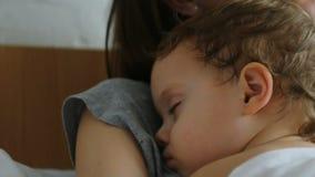 Bemuttern Sie und ihr kleines Baby im Bett im sonnigen Raum stock video