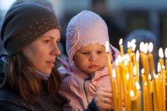 Bemuttern Sie und ihr kleines blondes Mädchen in der russischen Kirche Lizenzfreies Stockbild
