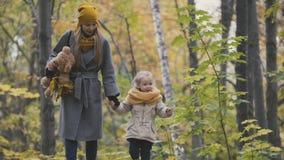 Bemuttern Sie und ihr kleines blondes Mädchen der Tochter, das in einen Herbstpark geht Stockfoto