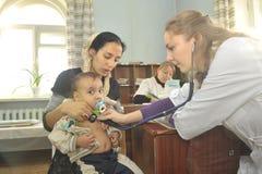 Bemuttern Sie und ihr kleines Kind an einer Aufnahme mit einem weiblichen Kinderarztdoktor lizenzfreies stockbild