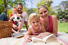 Bemuttern Sie und ihr Mädchen, das auf einer Picknicktischdecke liegt Lizenzfreies Stockbild