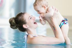 Bemuttern Sie und ihr neugeborenes Kind am Säuglingsschwimmkurs Lizenzfreies Stockfoto