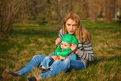 Bemuttern Sie und ihr Sohn, der auf dem Rasen sitzt Lizenzfreie Stockbilder