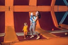 Bemuttern Sie und ihr Sohn, der auf eine Trampoline im Eignungspark springt und zuhause exersice tut stockfotografie
