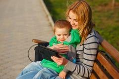 Bemuttern Sie und ihr Sohn, der mit einem Tabletten-PC spielt Stockbilder