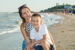 Bemuttern Sie und ihr Sohn, der Spaß auf dem Strand hat Lizenzfreie Stockfotos