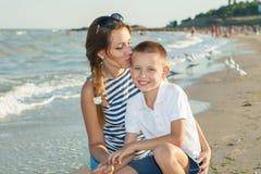 Bemuttern Sie und ihr Sohn, der Spaß auf dem Strand hat Stockfotos