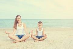 Bemuttern Sie und ihr Sohn, der Yoga auf Küste von Meer auf Strand tut Stockfotografie