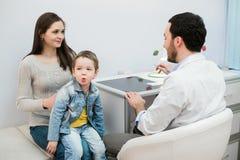 Bemuttern Sie und ihr Sohn mit lustigem Gesicht am Krankenhaus sprechend mit einem Doktor lizenzfreies stockfoto
