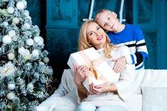 Bemuttern Sie und ihr Sohn zu Hause mit einem Weihnachtsbaum lizenzfreie stockfotos