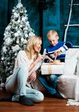 Bemuttern Sie und ihr Sohn zu Hause mit einem Weihnachtsbaum stockbilder