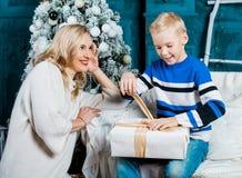 Bemuttern Sie und ihr Sohn zu Hause mit einem Weihnachtsbaum lizenzfreie stockbilder