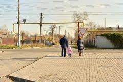 Bemuttern Sie und ihre Kinder, die Straße auf Schulweg kreuzen stockfotos