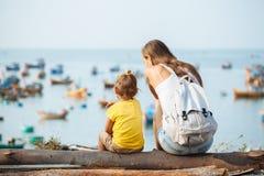 Bemuttern Sie und ihre kleine Tochter, die auf der Küste sitzt, die heraus über dem Ozean schaut stockfotos