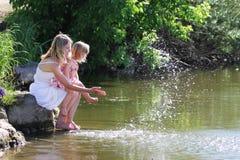 Bemuttern Sie und ihre kleine Tochter, die Wasser in dem See spritzt Lizenzfreie Stockfotografie
