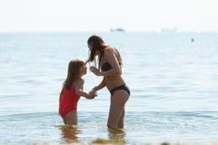 Bemuttern Sie und ihre Kleinkindtochter, die auf Strand spielt Lizenzfreies Stockfoto