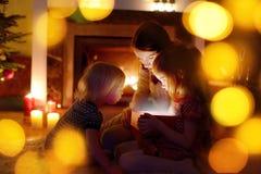 Bemuttern Sie und ihre Töchter, die ein Weihnachtsgeschenk öffnen lizenzfreies stockfoto