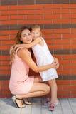 Bemuttern Sie und ihre Tochter, die draußen im Sommer spielt Stockfoto