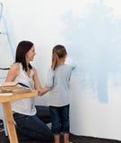 Bemuttern Sie und ihre Tochter, die eine Wand malt Lizenzfreie Stockfotos
